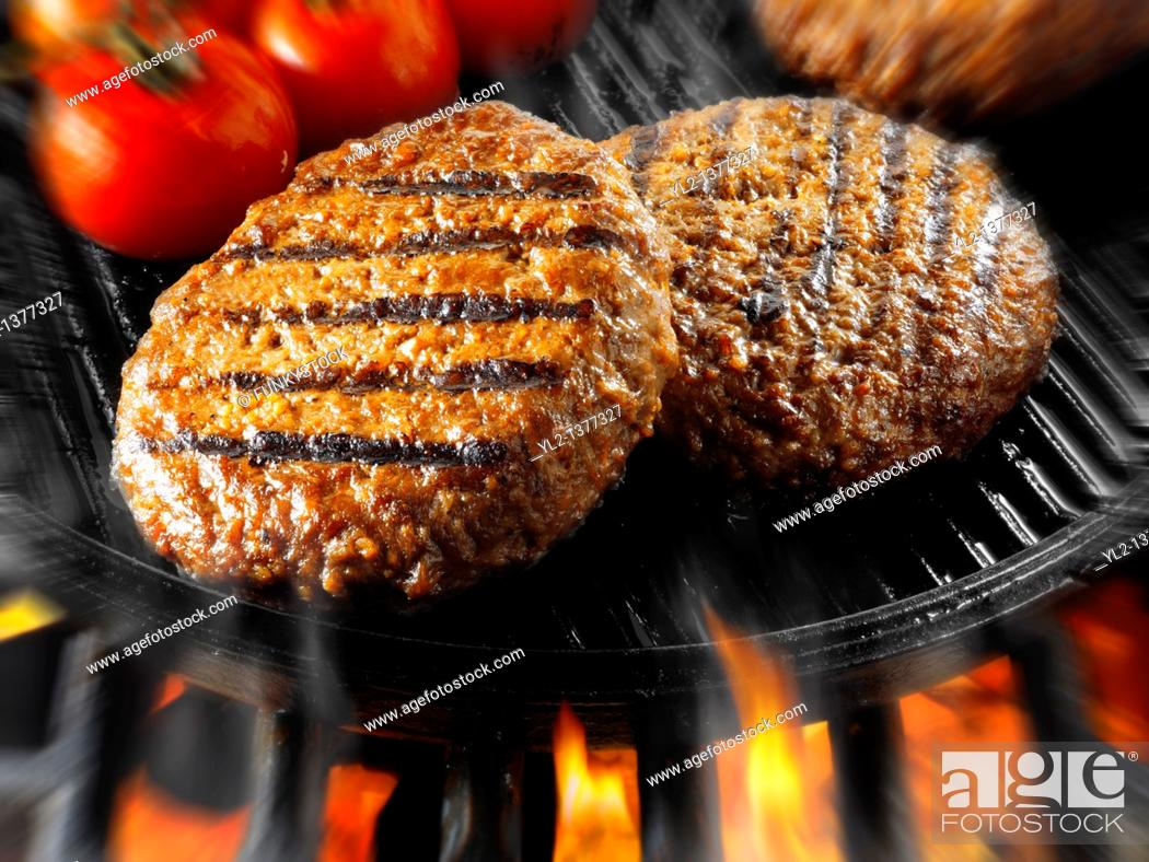 Stock Photo: Beef burgers being cooked in a skillet with flames.