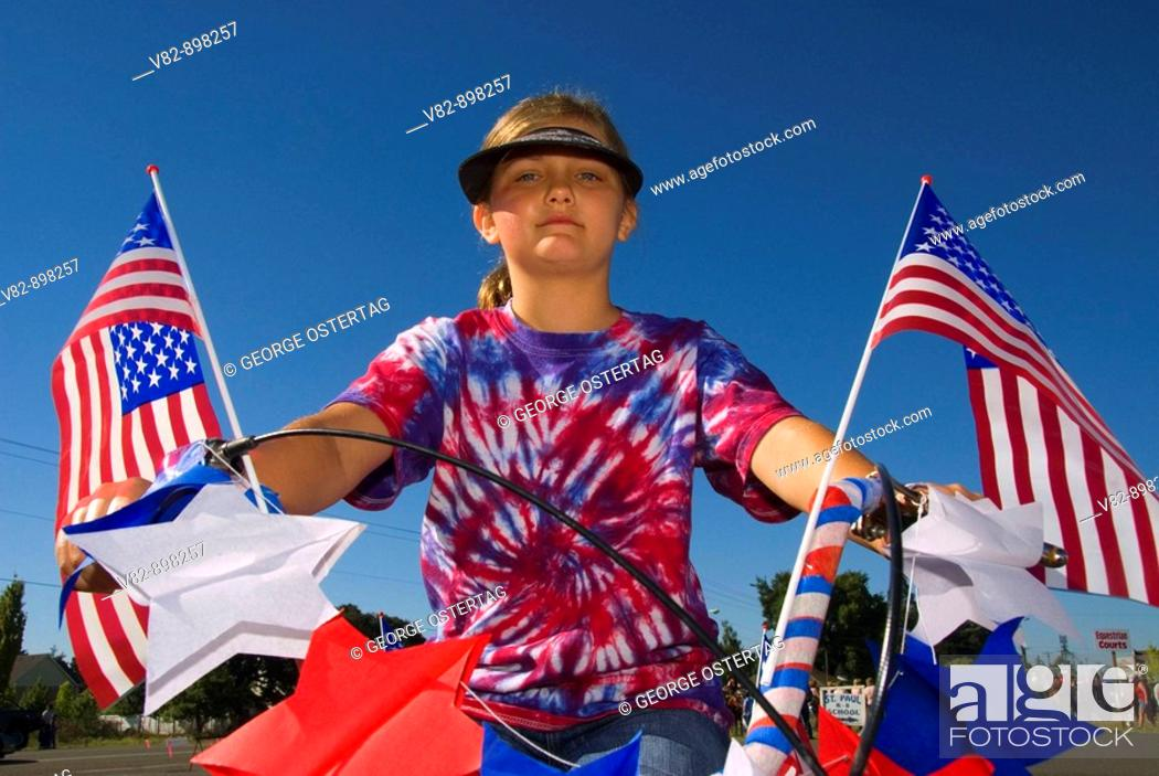 Stock Photo: OR36339 4th of July girl cyclist, St Paul Rodeo Parade, St Paul, OR.