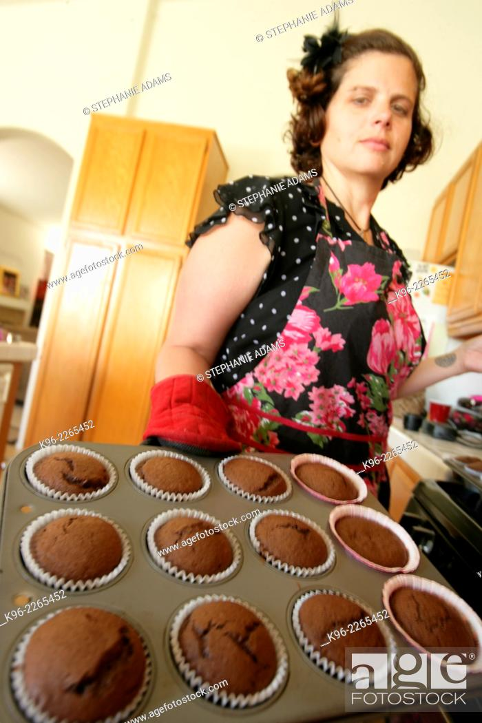 Stock Photo: Woman baking chocolate cupcakes in a kitchen.