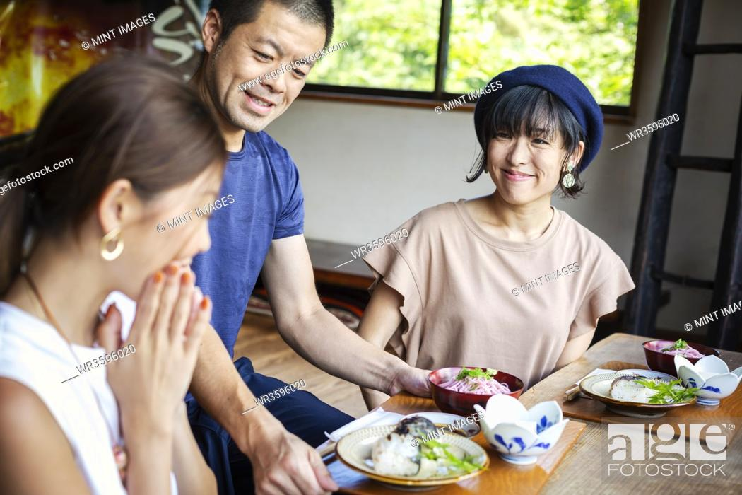 Stock Photo: Waiter serving two Japanese women sitting at a table in a Japanese restaurant.