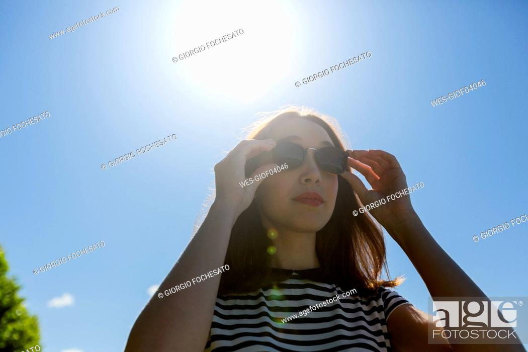 Stock Photo: Portrait of young woman at backlight wearing sunglasses.
