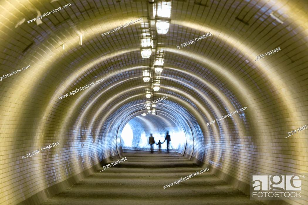 Stock Photo: light at the end of a tunnel - family of three walking.