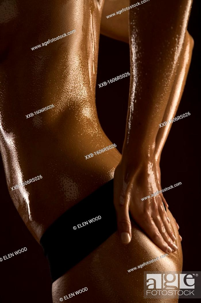 Stock Photo: woman applying oil on her bottom.