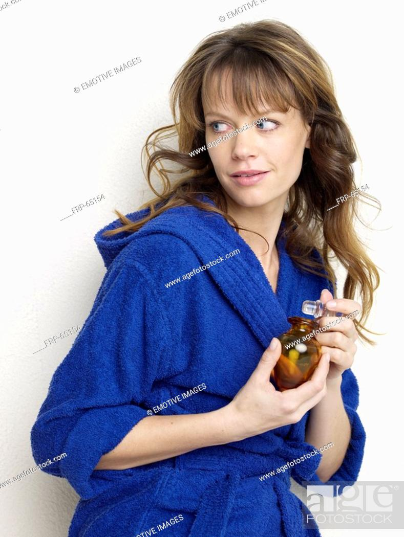 Stock Photo: Woman in blue bathrobe with small bottle.