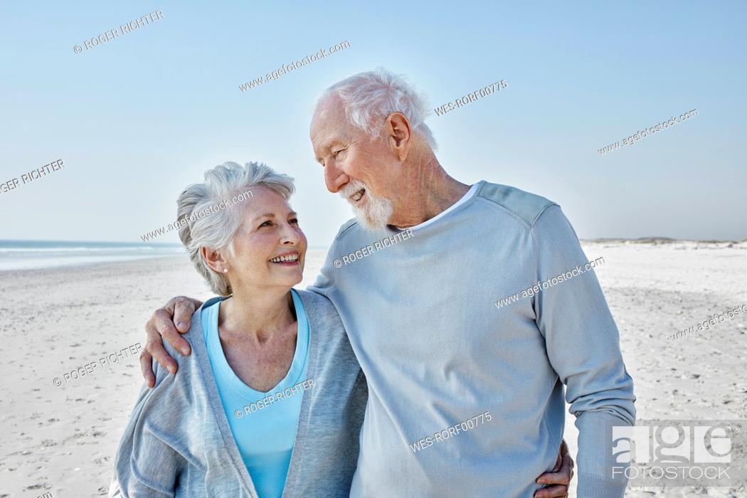 Photo de stock: Smiling senior couple on the beach.