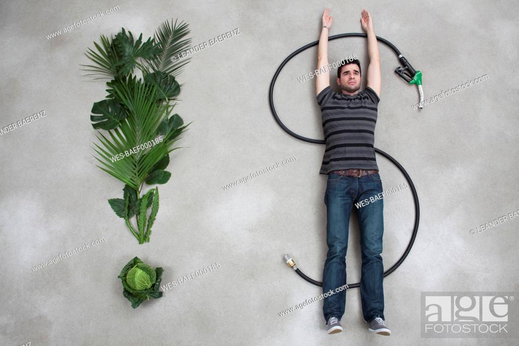 Stock Photo: Young man lying on industrial hose beside plant.