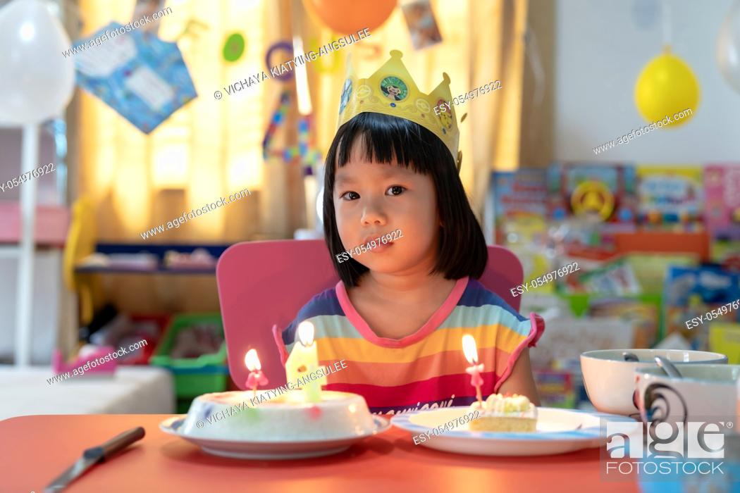 Stock Photo: Asian girl kid with her birthday cake celebrate alone with family because city lockdown while COVID-19 Pandemic. Celbration and quarantine concept.