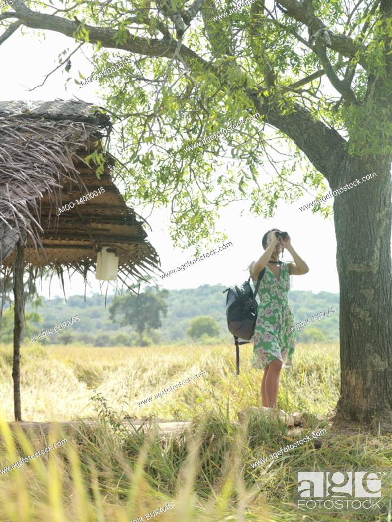 Stock Photo: Young woman looking through binoculars by thatched roof.