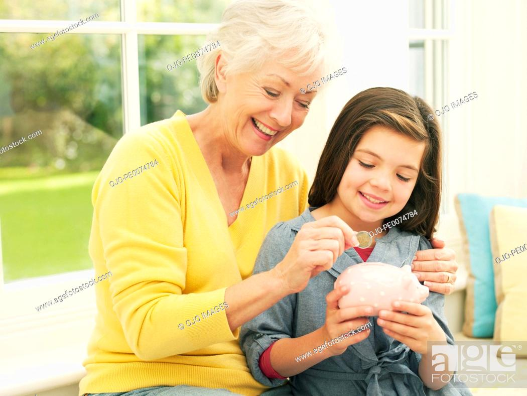 Stock Photo: Grandmother putting coin into granddaughter's piggy bank.