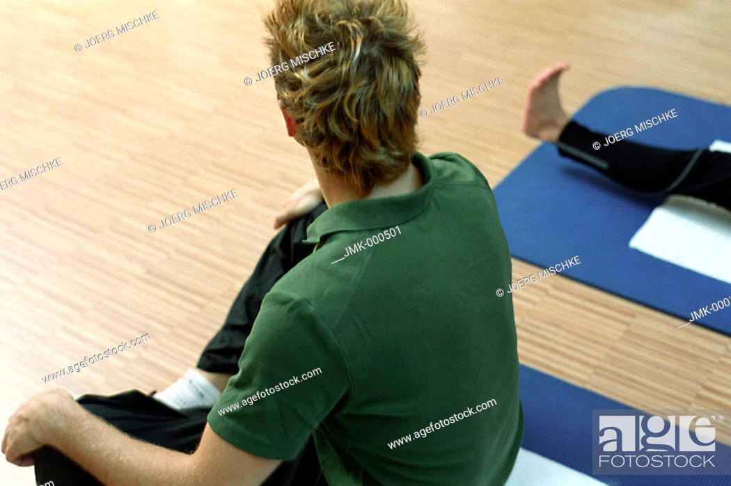 Stock Photo: Young man at the fitness studio, gym, sitting on a mat, making gymnastics.