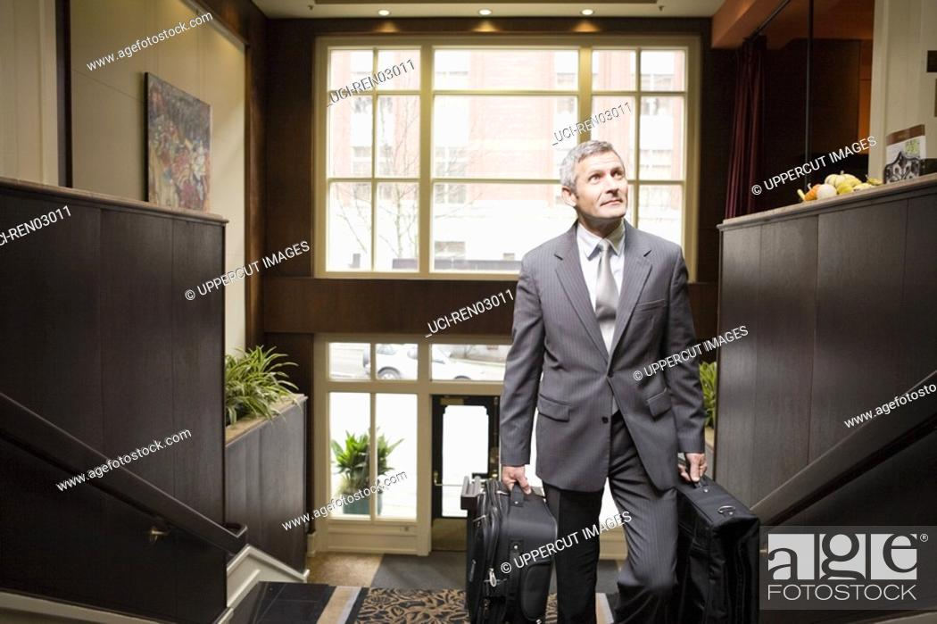 Stock Photo: Businessman carrying suitcases up stairs.