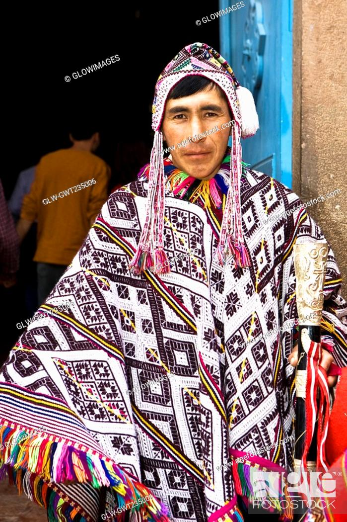 Stock Photo: Portrait of a young man wearing a traditional clothing and holding a stick, Peru.