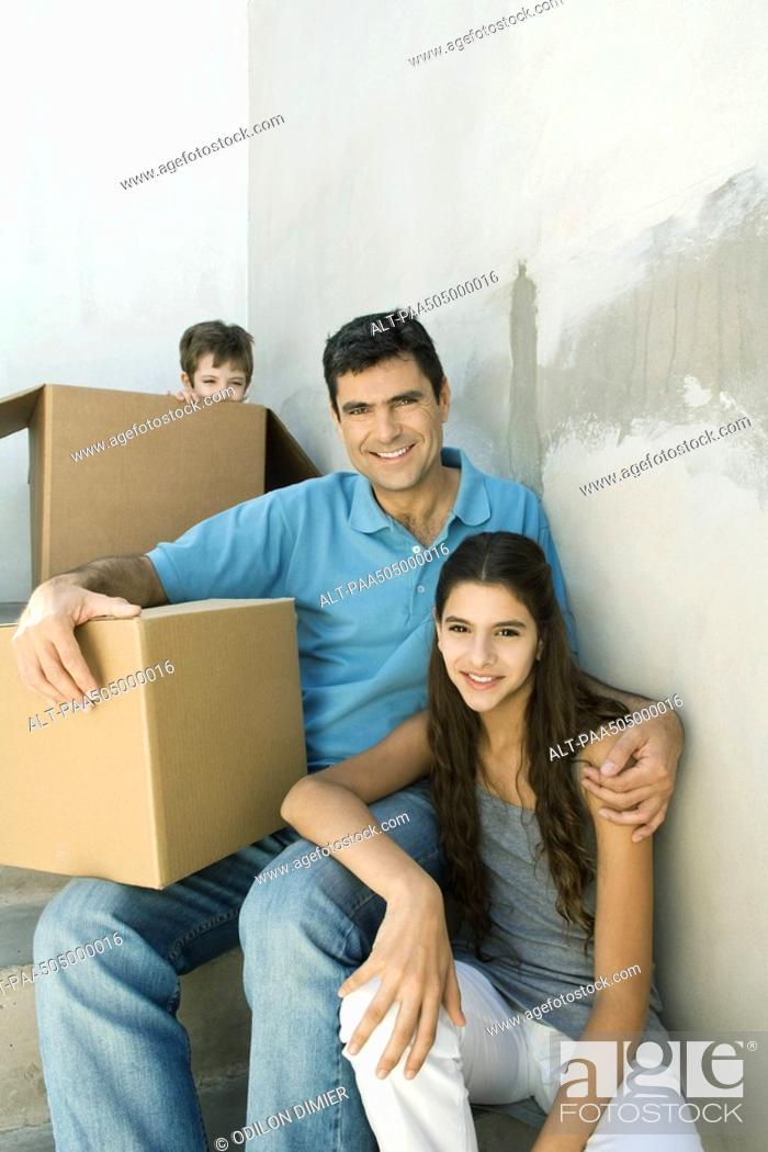 Stock Photo: Father and teen daughter on stairwell with cardboard boxes, boy hiding in background.