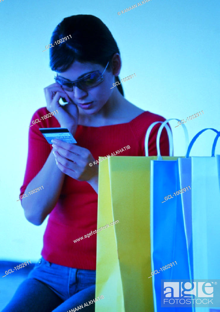 Stock Photo: Woman checking her credit card limits during shopping.