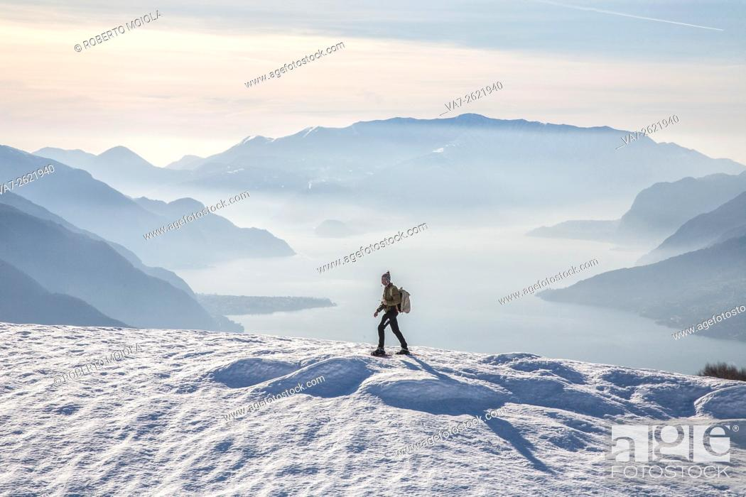 Stock Photo: Winter view of Lake Como while a hiker proceeds with snowshoes Vercana mountains High Lario Lombardy Italy Europe.