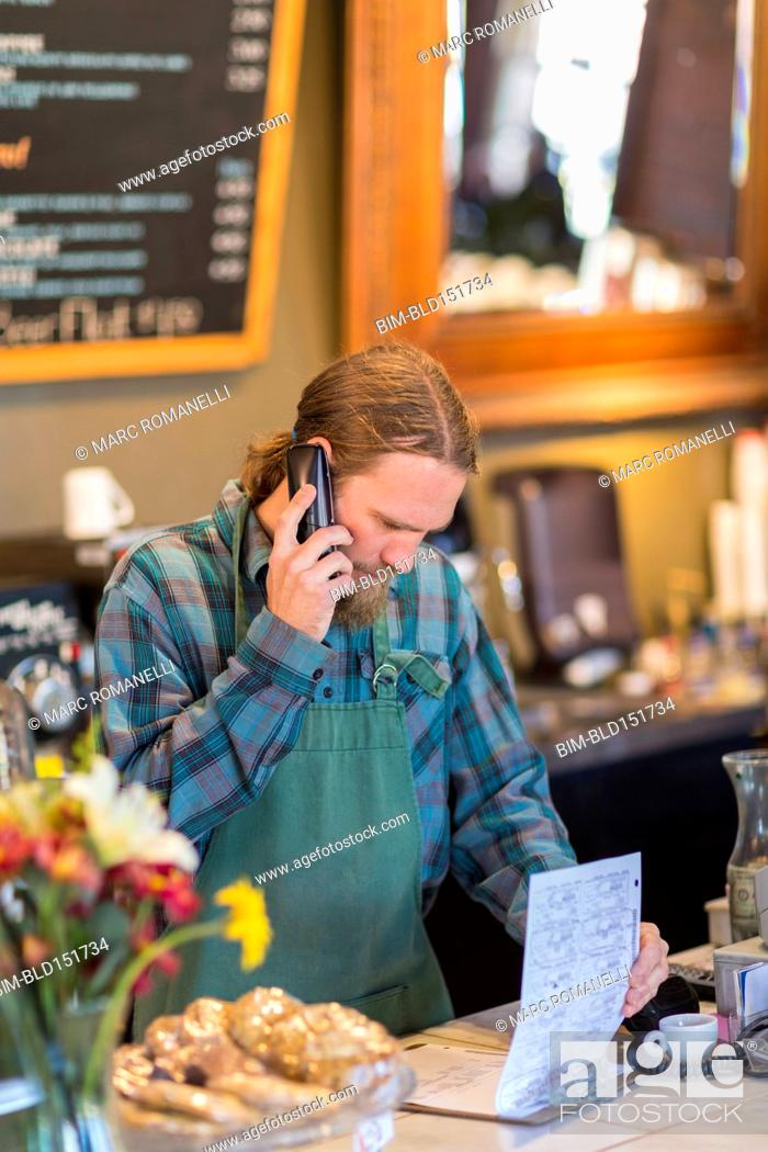 Stock Photo: Caucasian server on telephone reading clipboard in cafe.
