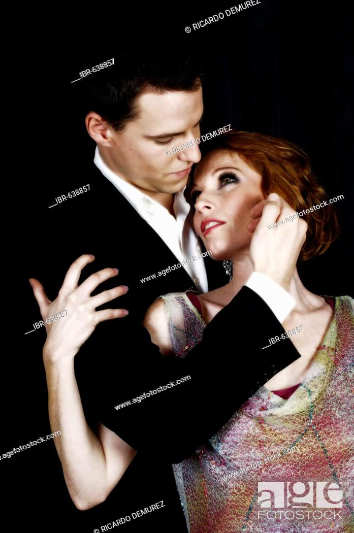 65ce9be9977e Stock Photo - Young couple dressed in evening wear caressing each other