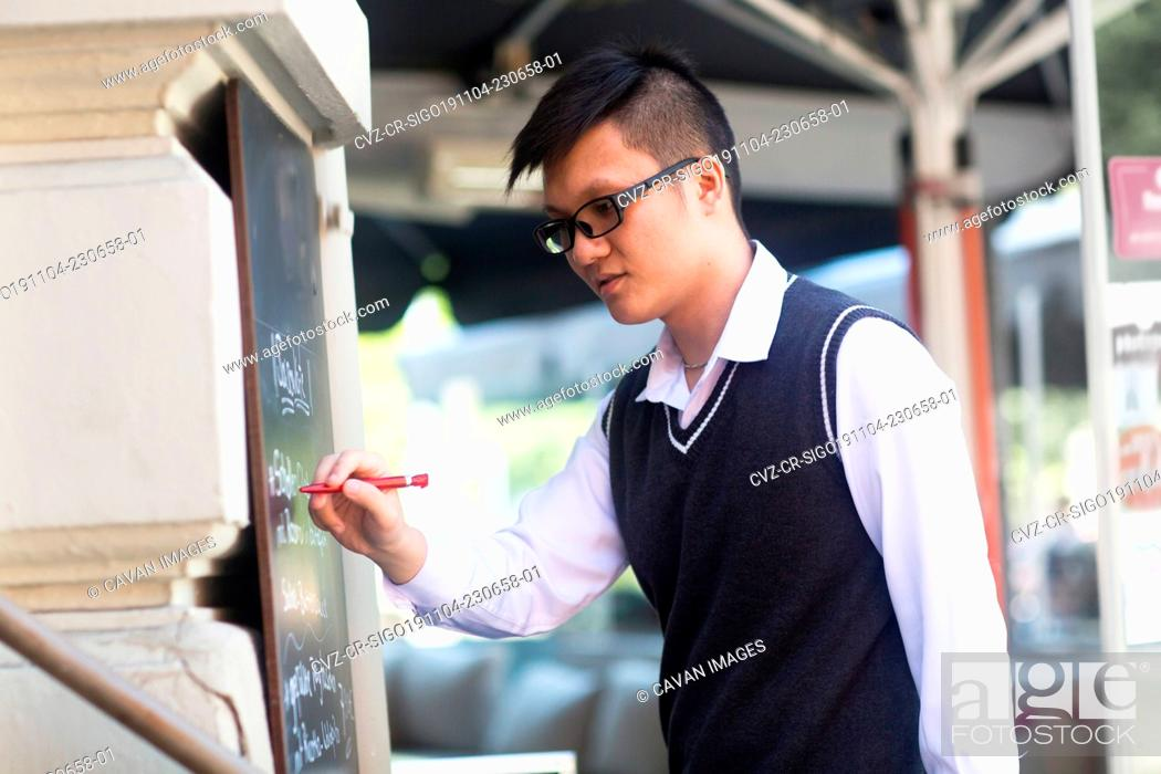 Imagen: young asia waiter in a bar writing new offers.