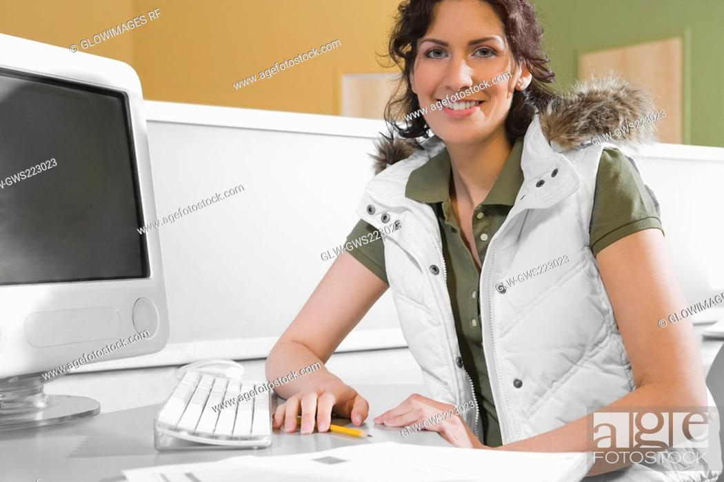 Stock Photo: Portrait of a young woman sitting in front of a desktop PC and smiling.