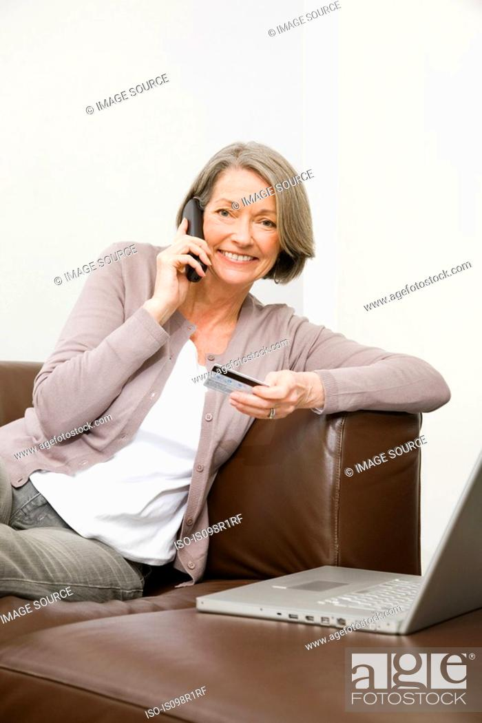 Stock Photo: Mature woman using telephone banking.
