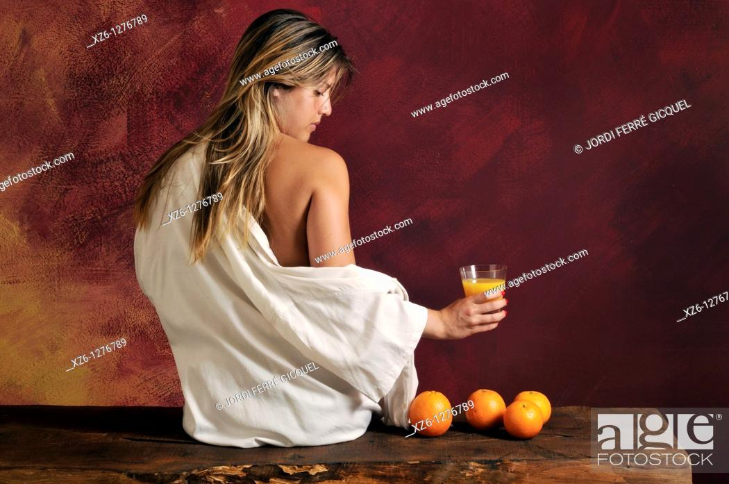 Imagen: half-naked young woman witht oranges and orange juice.