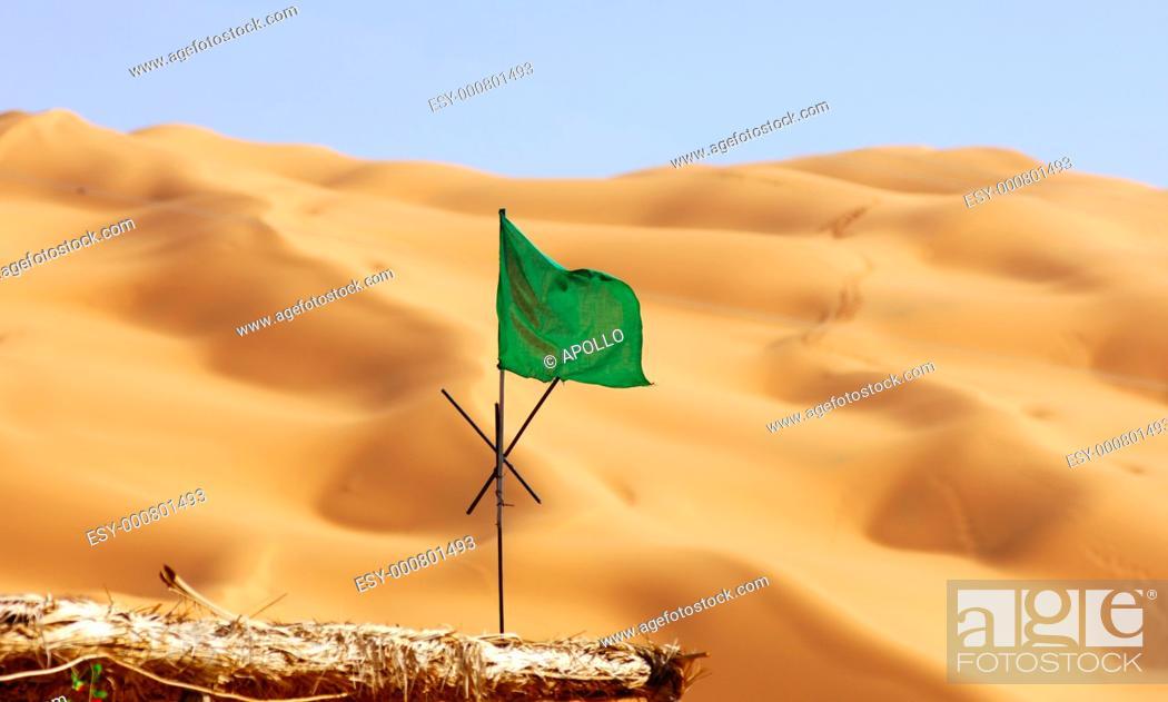 Stock Photo: National flag of Libya in front of sand dunes of the Sahara desert, Awbari Sand Sea, Libya.