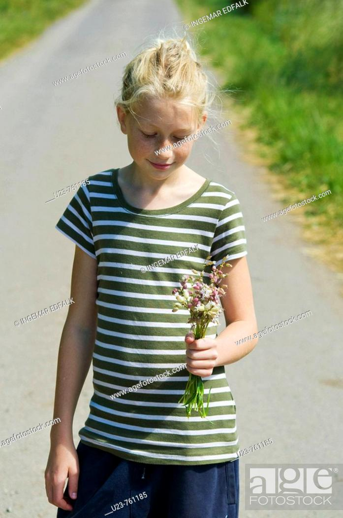 Stock Photo: Young girl with flowers in her hand.
