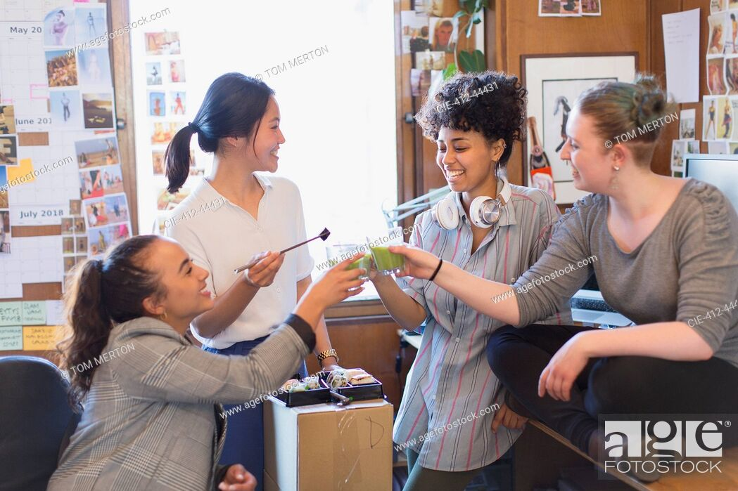 Imagen: Creative female designers toasting green smoothies in office.