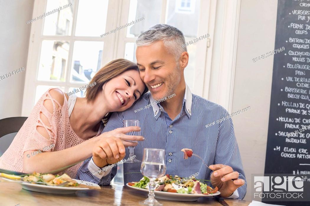 Stock Photo: Caucasian couple cuddling in restaurant.