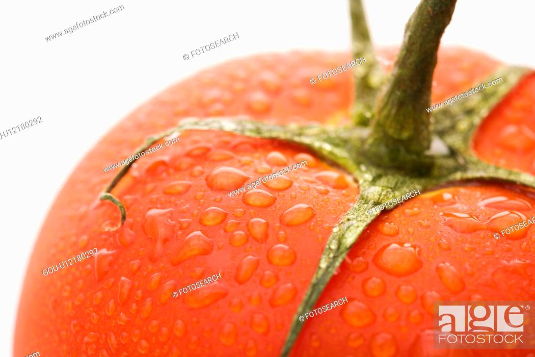 Stock Photo: Close up of wet red ripe tomato against white background.