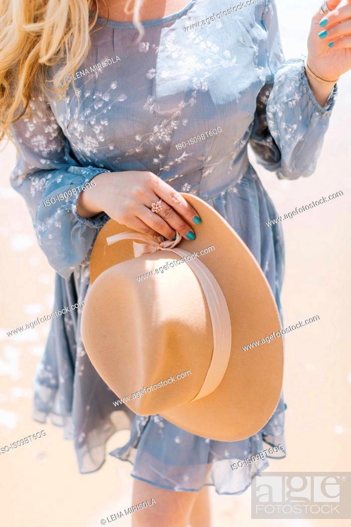 Stock Photo: Young woman holding felt hat on beach, mid section, Menemsha, Martha's Vineyard, Massachusetts, USA.