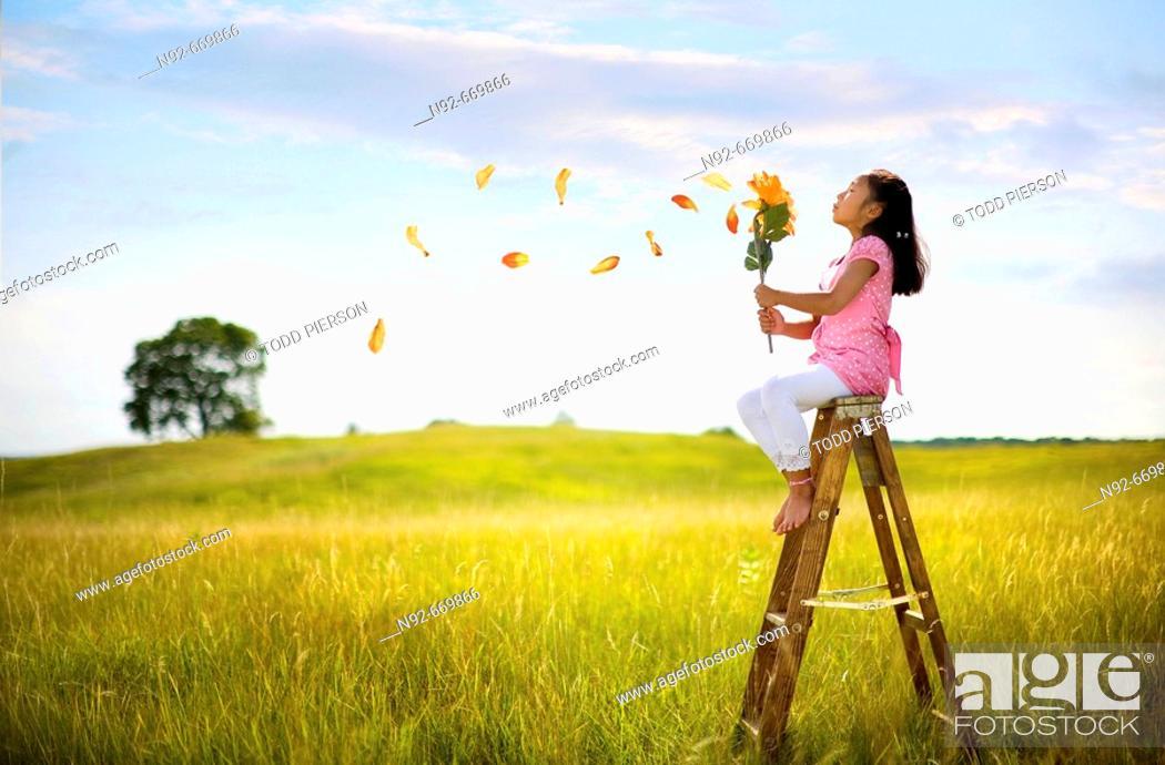 Stock Photo: Girl blowing big flower petals.  Illinois.