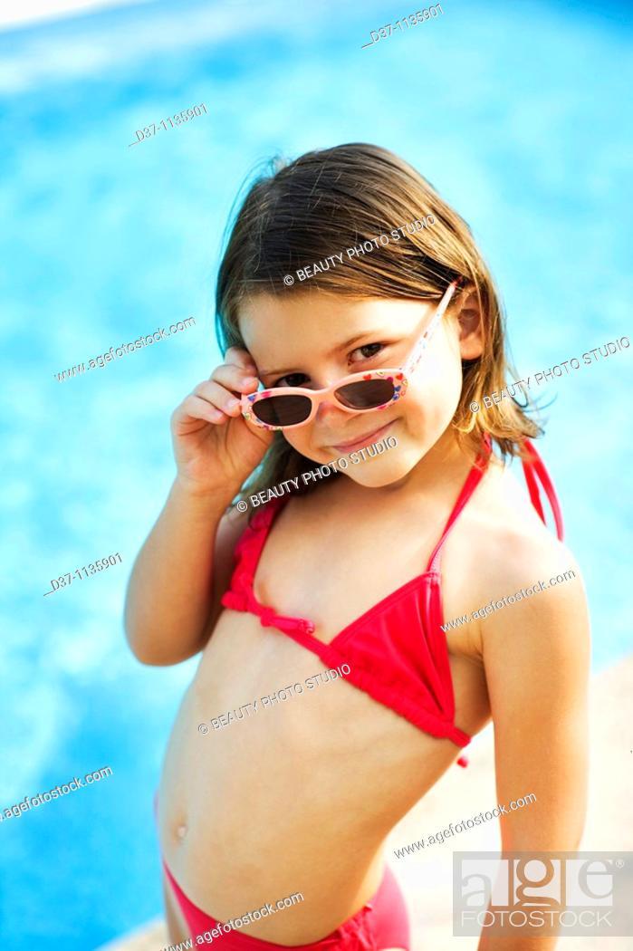 Photo de stock: Young girl in bikini, looking over sunglasses.