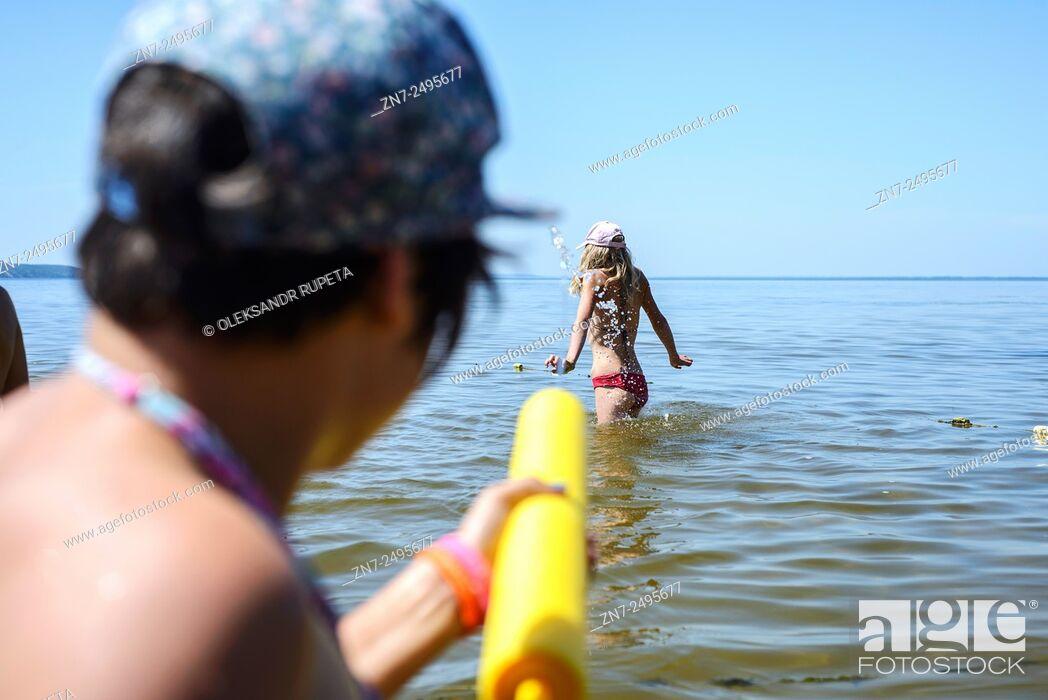 Stock Photo: Girl playing with water gun in Ukrainian scout training camp, Kiev region, Ukraine.