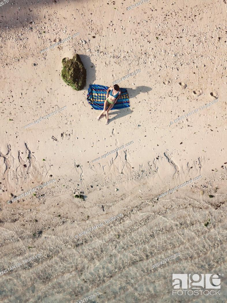 Stock Photo: Woman relaxing on towel on the beach, top view.