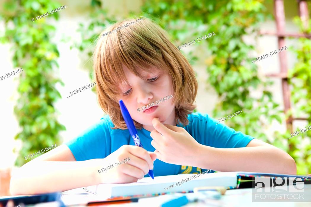 Stock Photo: Boy with Blond Hair Doing Homework Outdoors.