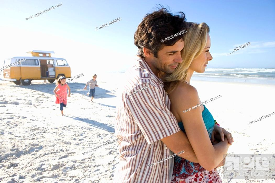 Stock Photo: Man embracing woman on beach, children 5-9 in background, side view.