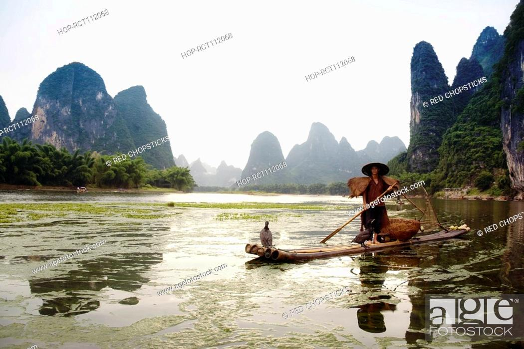 Stock Photo: Fisherman on a bamboo raft with a hill range in the background, Guilin Hills, XingPing, Yangshuo, Guangxi Province, China.