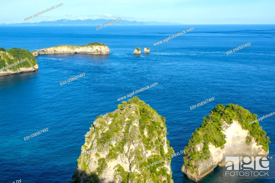 Imagen: Indonesia. A few rocky islets with jungle. Mountains and clouds on the horizon.