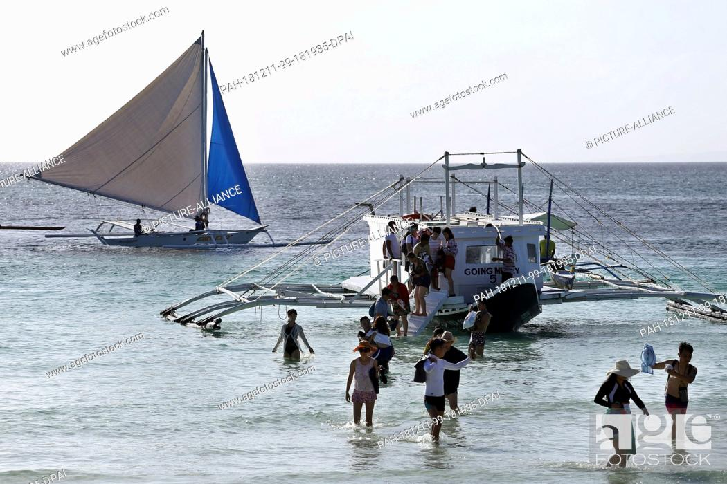 Stock Photo: 09 December 2018, Philippines, Boracay: A group of tourists get off a boat at the beach. The beaches of the island of Boracay were closed to the public for six.
