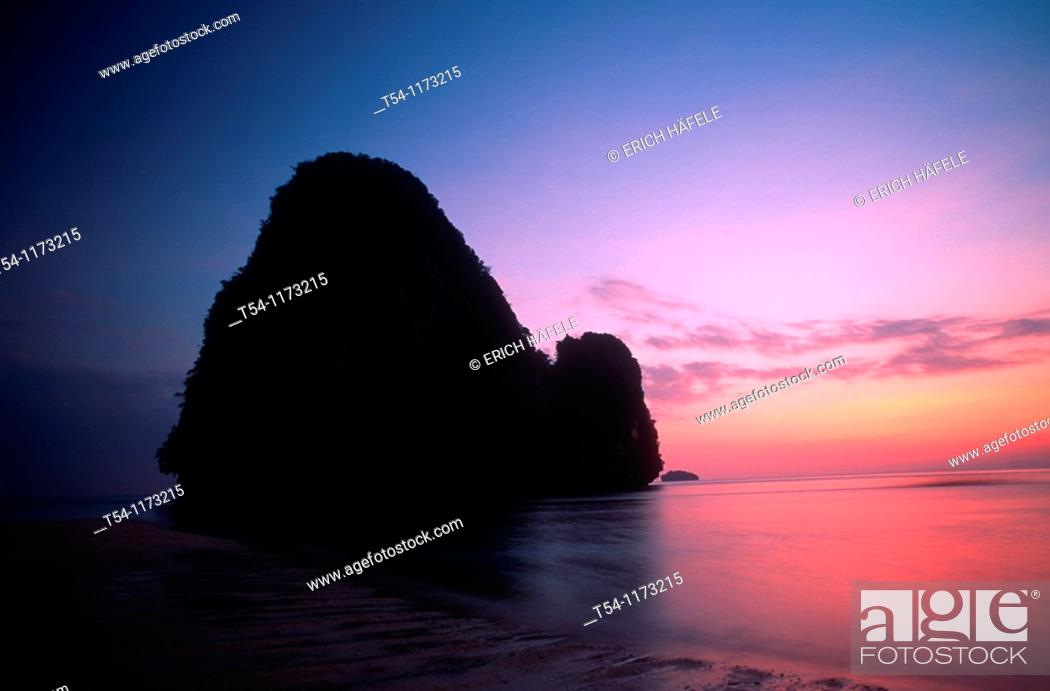 Stock Photo: Silhouette of a rock in the sea at sunset.