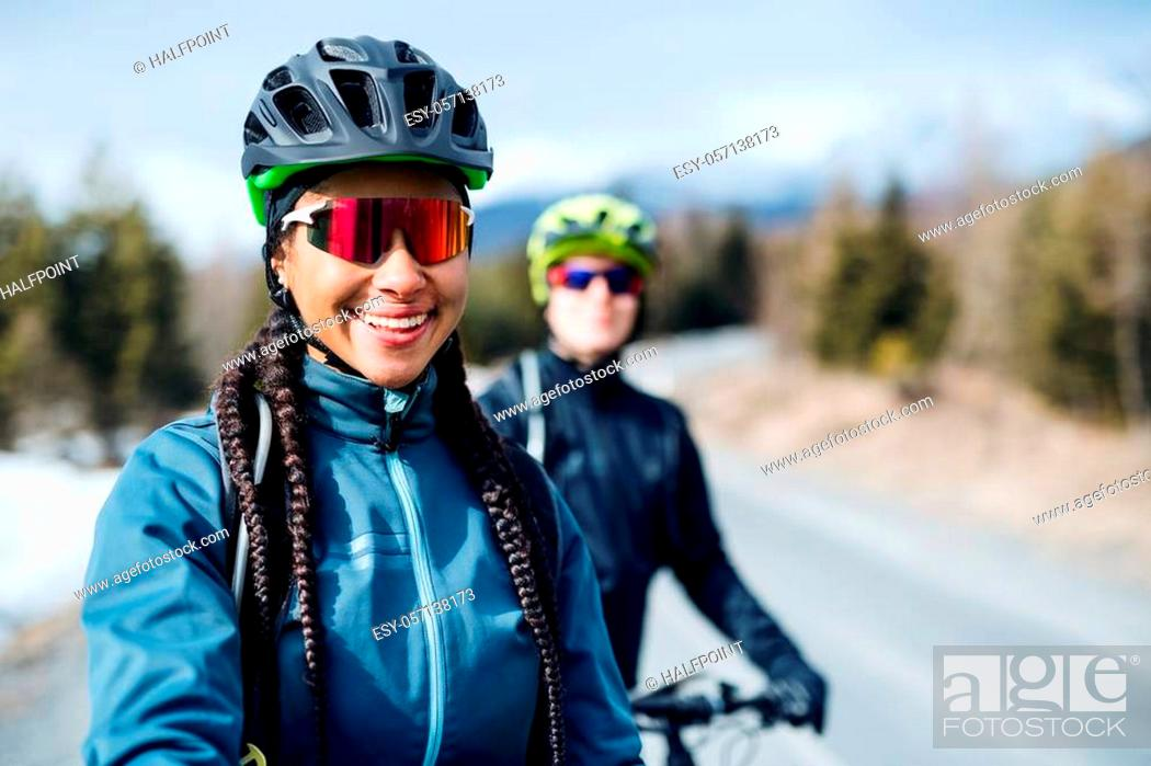 Stock Photo: Two mountain bikers riding on road outdoors in winter, looking at camera.