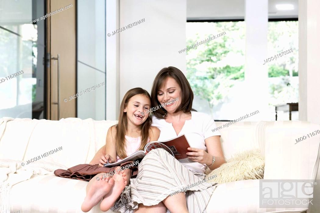 Stock Photo: Mother and daughter reading book in living room portrait.
