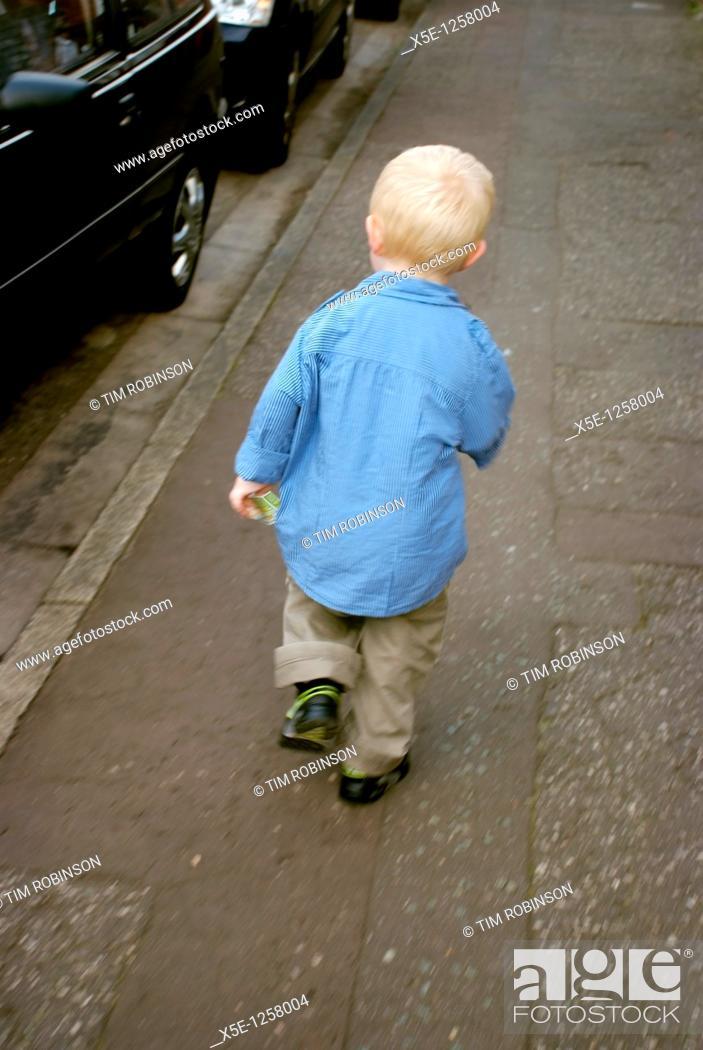 Stock Photo: Rearview 4 year blonde boy jogging along suburban pavement.