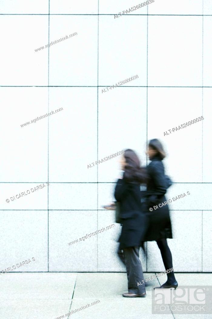 Stock Photo: Two businesswomen walking side by side down sidewalk.