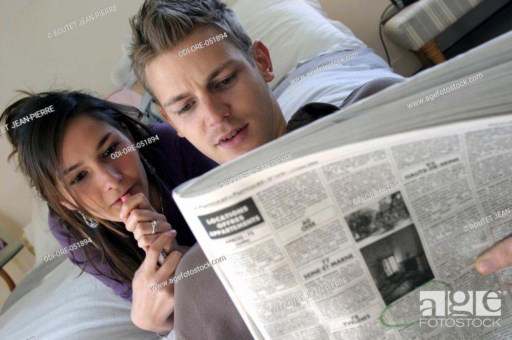 Stock Photo: teenagers inside girl couple boy discussion friends lovers ying down pen choose movement hand read reading newspaper small ads looking for property market.