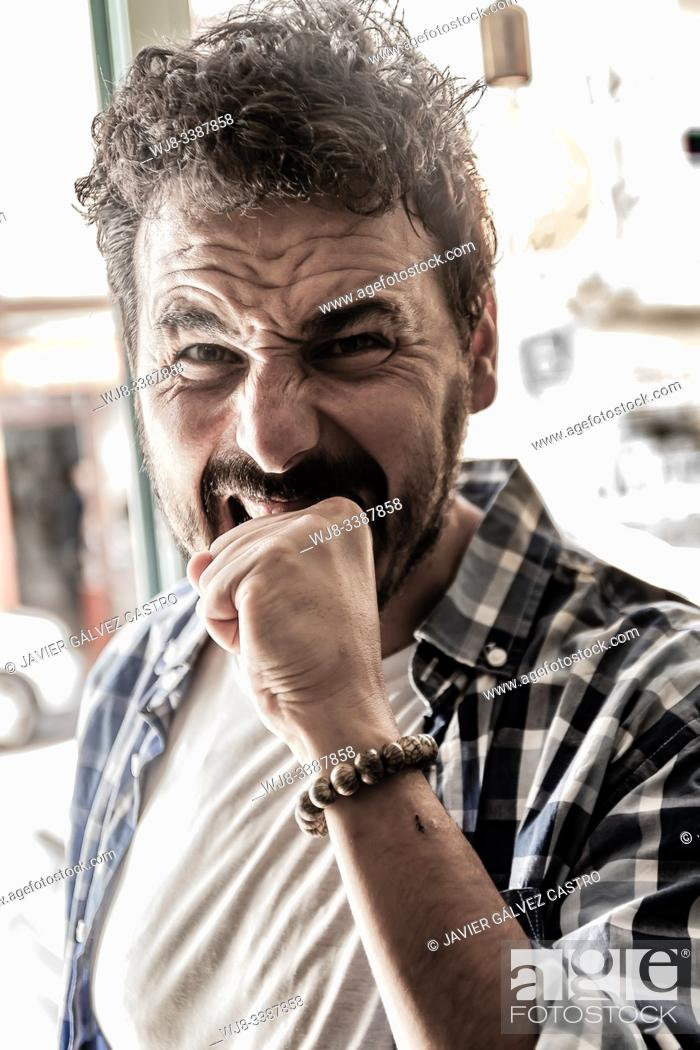 Stock Photo: Young man biting his hand in funny pose.