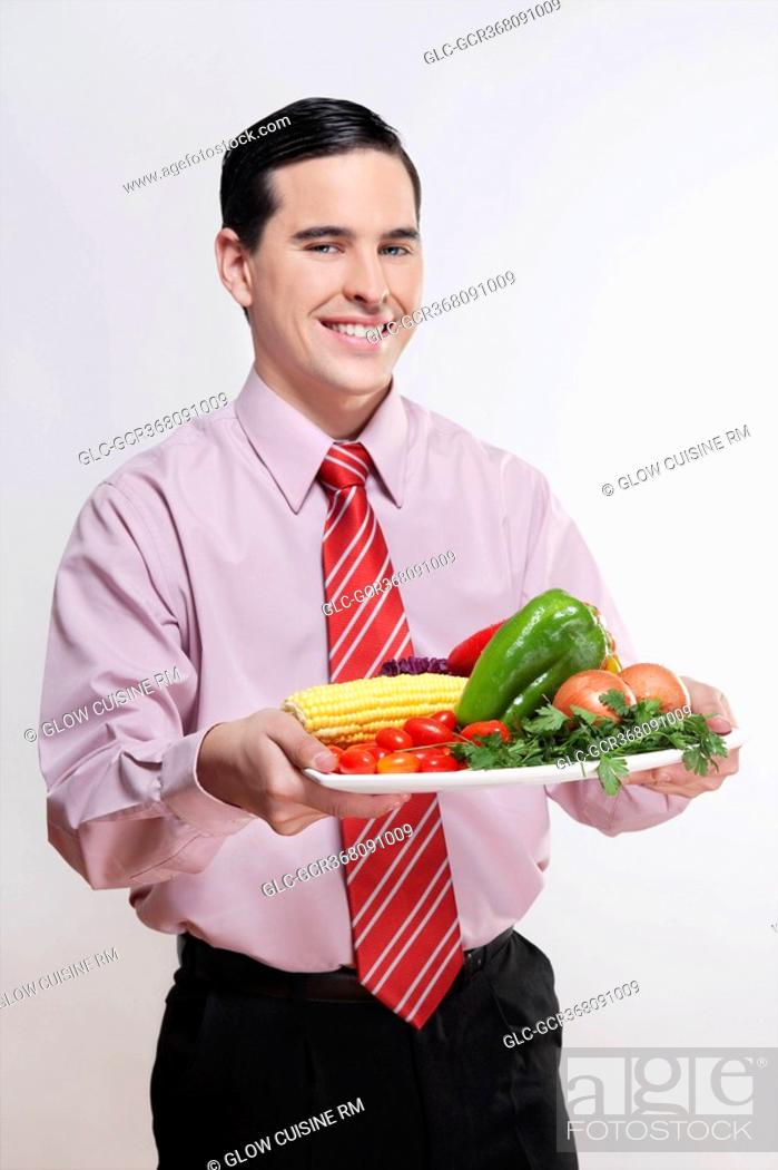 Stock Photo: Businessman holding a platter of fresh vegetables.