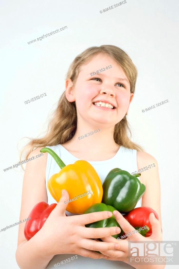 Stock Photo: Girl holding peppers.