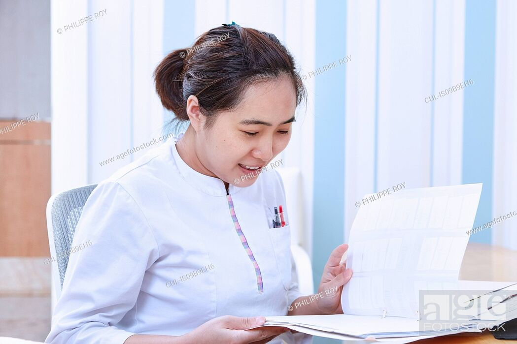 Stock Photo: Doctor reading medical records.